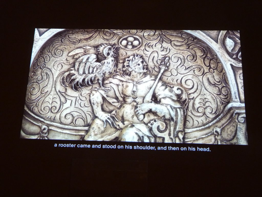 Hi-res photos of individual scenes from the dishes are projected overhead to clarify the images, in this case the rooster that settled on Vitellius' shoulder and then stood on his head while he judged at a tribunal in Vienna