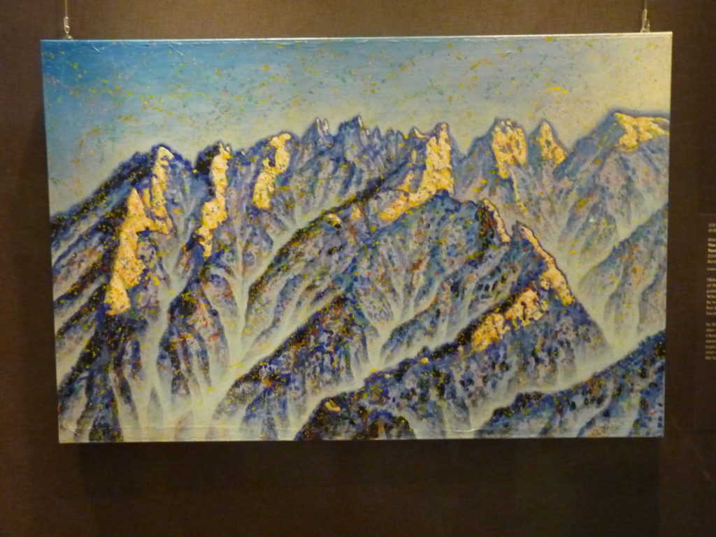 Shin Jangsik, Korean, born 1959. The Light at Cheonhwadae Peaks, from the series Twelve Scenes of Mount Geumgang, Korea, 2014 Acrylic on canvas and Korean paper. Image: 25 3/8 x 38 1/2 in. (64 x 98 cm). Lent by the artist Shin has almost exclusively devoted his energy to the subject of the Diamond Mountains since the early 1990s. He began painting the mountains in 1993 before ever visiting them. When the Diamond Mountains reopened to tourism in 1998, he was on the first ship sailing for Geumgang. Since then, he has journeyed multiple times, through different routes and locations and at all times of the year. In 2014 he painted a series of twelve scenes depicting various sites within the mountains in the four seasons. The Light at Cheonhwadae captures the brilliant sunlight reflected off the   snowcapped peaks. Shin, who trained in Western techniques, typically uses acrylic on canvas (or on Korean mulberry paper over canvas), capturing the effervescence and luminosity of the landscape in bright colors.