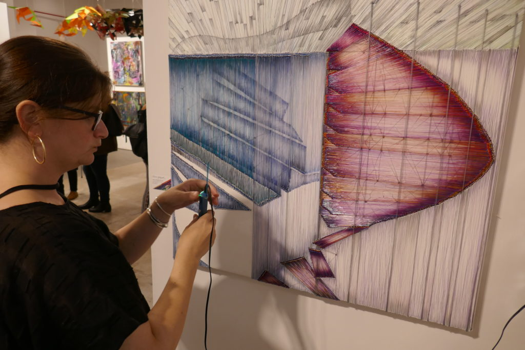 Rachel Goldsmith creates her paintings with an electric pen that extrudes her chosen color in plastic onto a surface formed by an array of wires